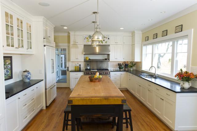 Inspiration for a large timeless u-shaped medium tone wood floor and brown floor open concept kitchen remodel in Salt Lake City with a double-bowl sink, white cabinets, soapstone countertops, paneled appliances, raised-panel cabinets, white backsplash, ceramic backsplash, an island and black countertops