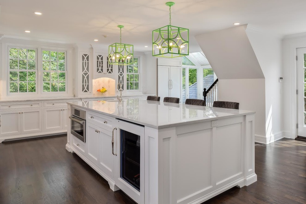 Inspiration for a large transitional l-shaped dark wood floor and brown floor eat-in kitchen remodel in New York with an undermount sink, recessed-panel cabinets, white cabinets, marble countertops, beige backsplash, marble backsplash, paneled appliances and an island