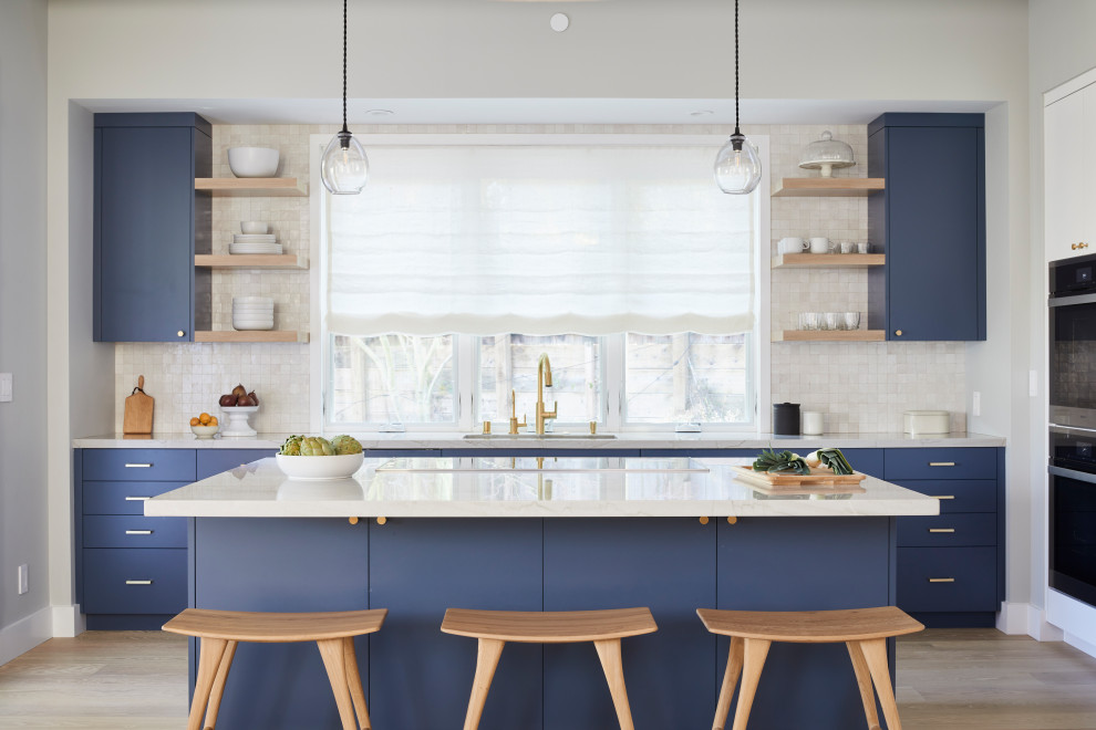 Danish l-shaped light wood floor and beige floor kitchen photo in San Francisco with an undermount sink, flat-panel cabinets, blue cabinets, stainless steel appliances, an island and white countertops