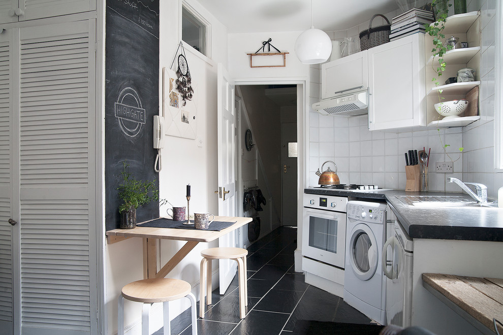 Example of a small danish single-wall black floor kitchen design in London with shaker cabinets, white cabinets, white backsplash, ceramic backsplash and white appliances