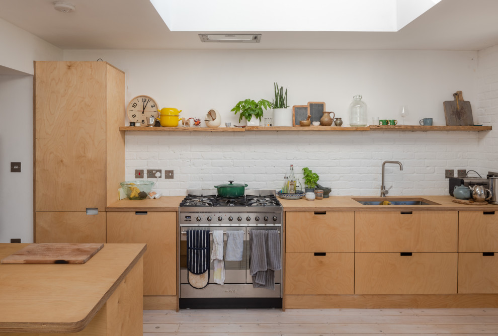 Inspiration for a scandinavian galley light wood floor and beige floor kitchen remodel in London with flat-panel cabinets, light wood cabinets, wood countertops, an island, an undermount sink, white backsplash, brick backsplash, stainless steel appliances and beige countertops