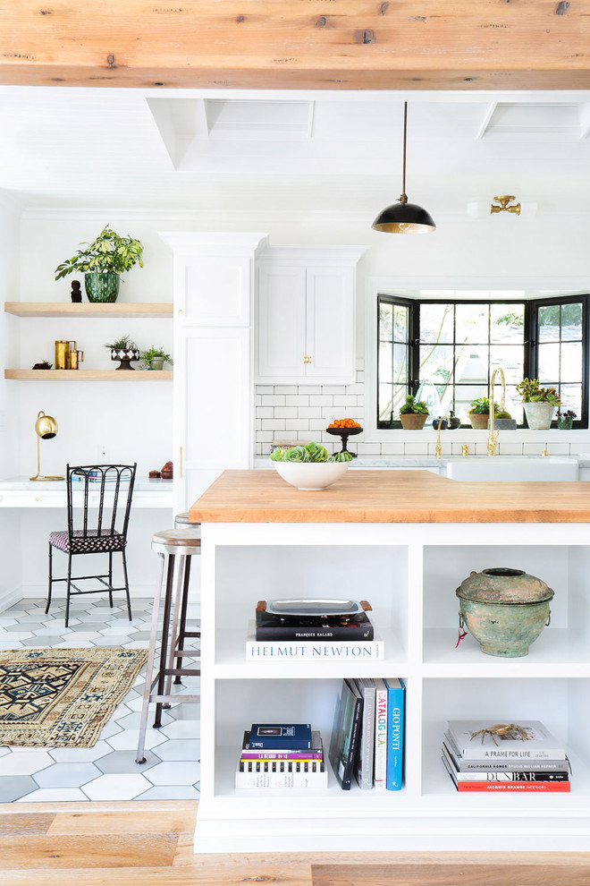 Open concept kitchen - mid-sized scandinavian porcelain tile open concept kitchen idea in Los Angeles with a farmhouse sink, recessed-panel cabinets, white cabinets, white backsplash, subway tile backsplash, stainless steel appliances, a peninsula and wood countertops