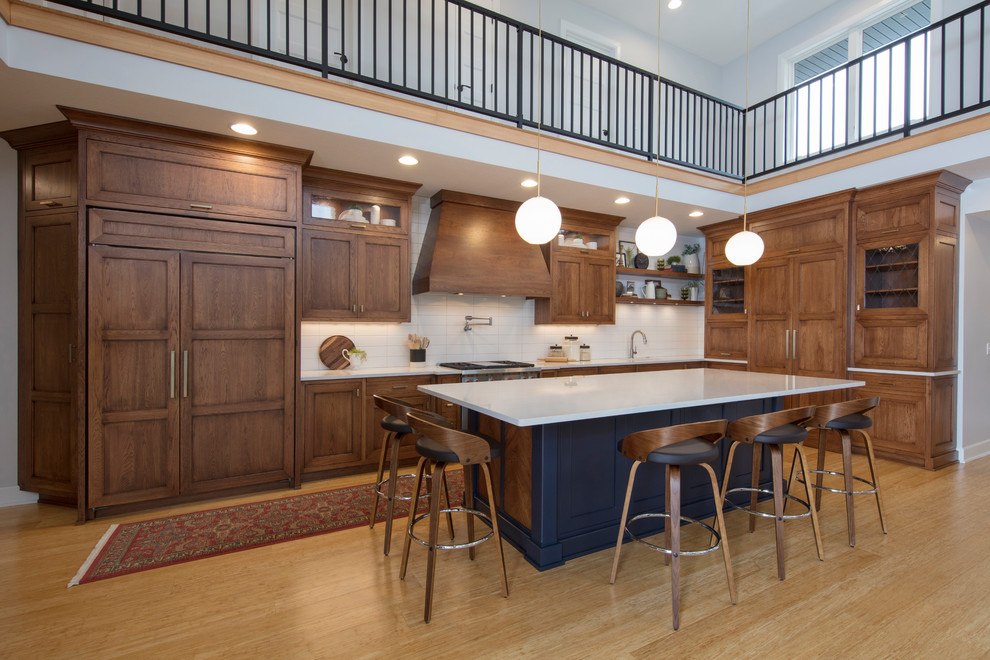 Kitchen - large transitional l-shaped medium tone wood floor and brown floor kitchen idea in Cleveland with an undermount sink, white backsplash, subway tile backsplash, an island, white countertops, medium tone wood cabinets and shaker cabinets