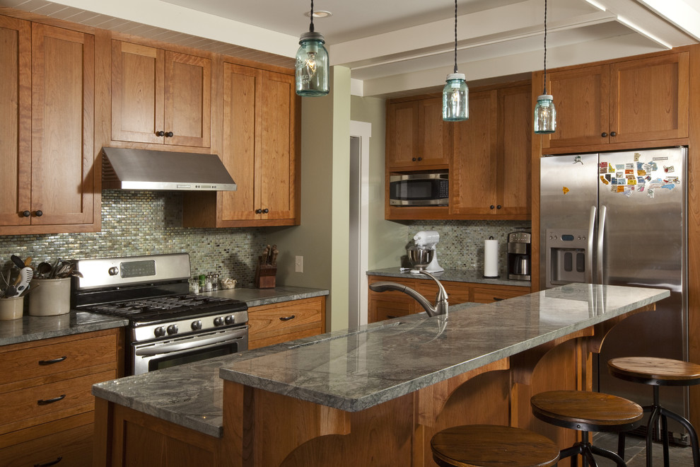 Example of a classic kitchen design in Minneapolis with mosaic tile backsplash, stainless steel appliances, green backsplash, shaker cabinets, medium tone wood cabinets and granite countertops