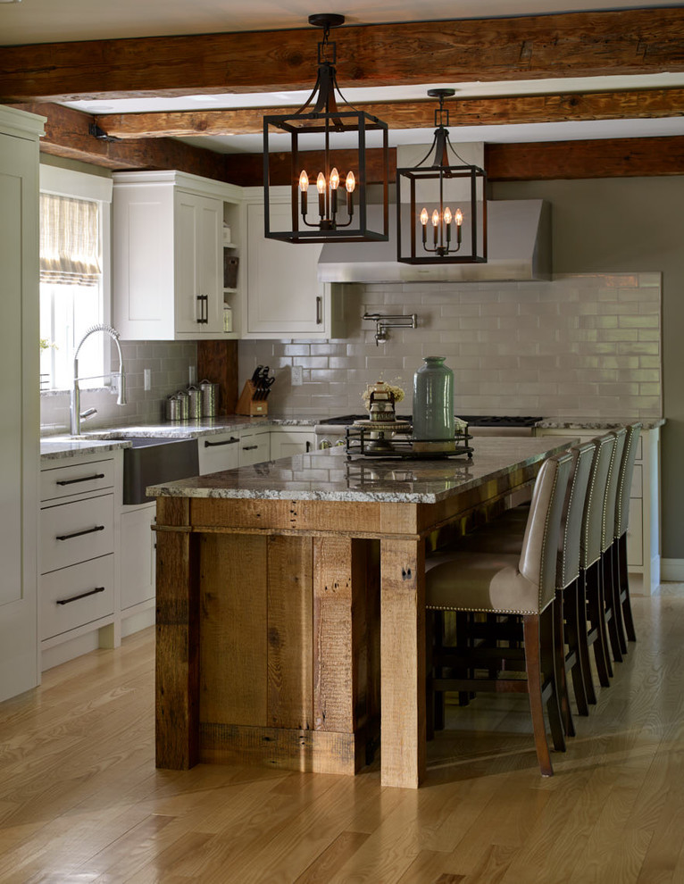 Large cottage light wood floor and beige floor eat-in kitchen photo in Portland Maine with a farmhouse sink, shaker cabinets, white cabinets, granite countertops, gray backsplash, subway tile backsplash, paneled appliances, an island and multicolored countertops