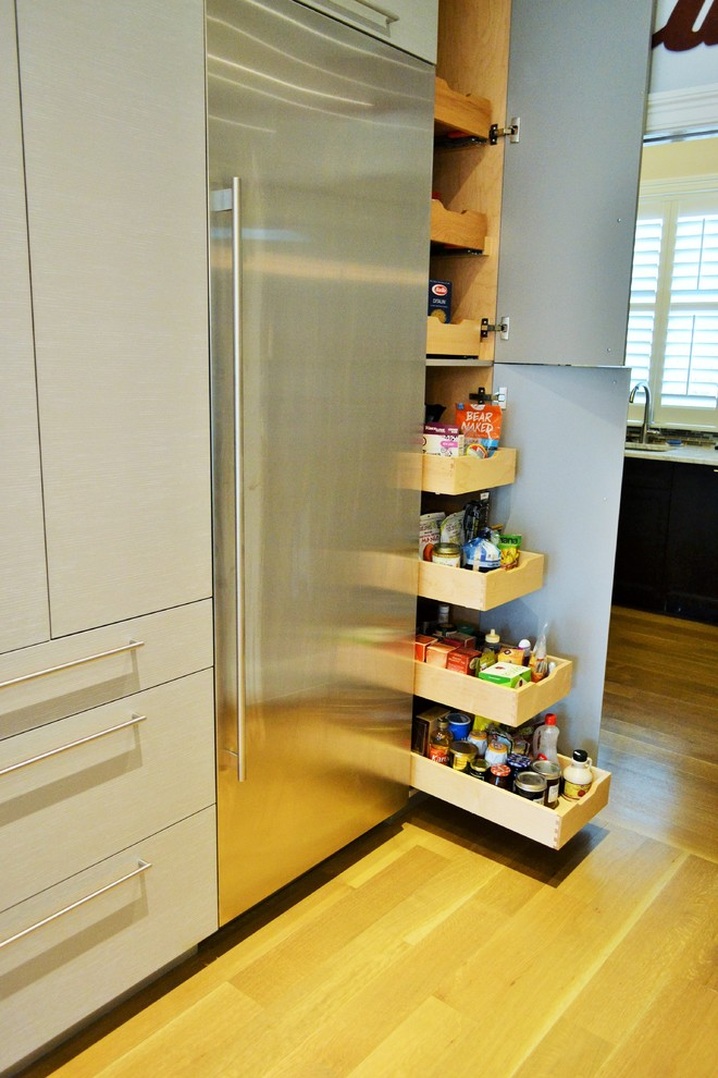 Large trendy l-shaped light wood floor kitchen pantry photo in New York with an undermount sink, glass-front cabinets, light wood cabinets, white backsplash, glass tile backsplash, stainless steel appliances and an island
