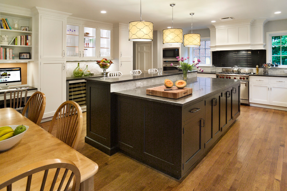 Enclosed kitchen - large transitional u-shaped medium tone wood floor and brown floor enclosed kitchen idea in New York with shaker cabinets, stainless steel appliances, an undermount sink, white cabinets, an island, granite countertops, black countertops, gray backsplash and glass tile backsplash