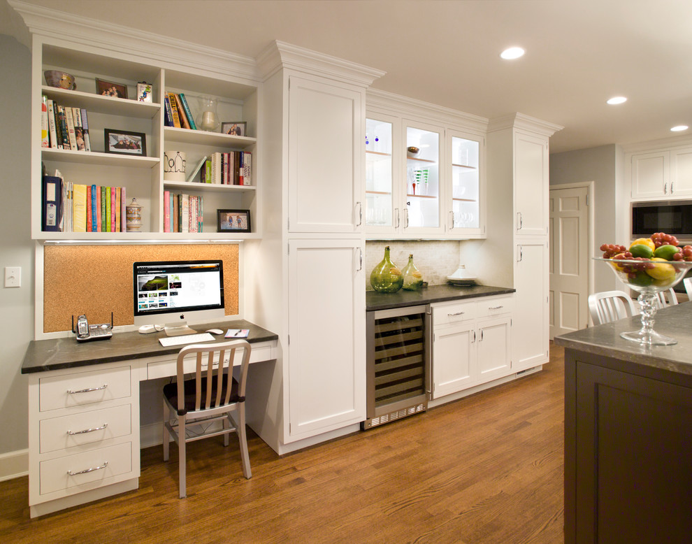 Example of a large transitional u-shaped medium tone wood floor and brown floor enclosed kitchen design in New York with shaker cabinets, white cabinets, an undermount sink, white backsplash, marble backsplash, stainless steel appliances, an island, granite countertops and black countertops