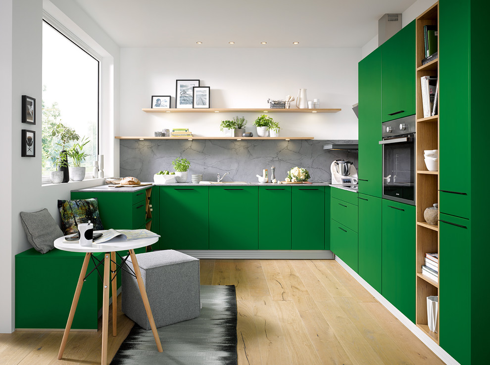 Trendy u-shaped light wood floor and beige floor kitchen photo in Other with flat-panel cabinets, green cabinets, gray backsplash and paneled appliances