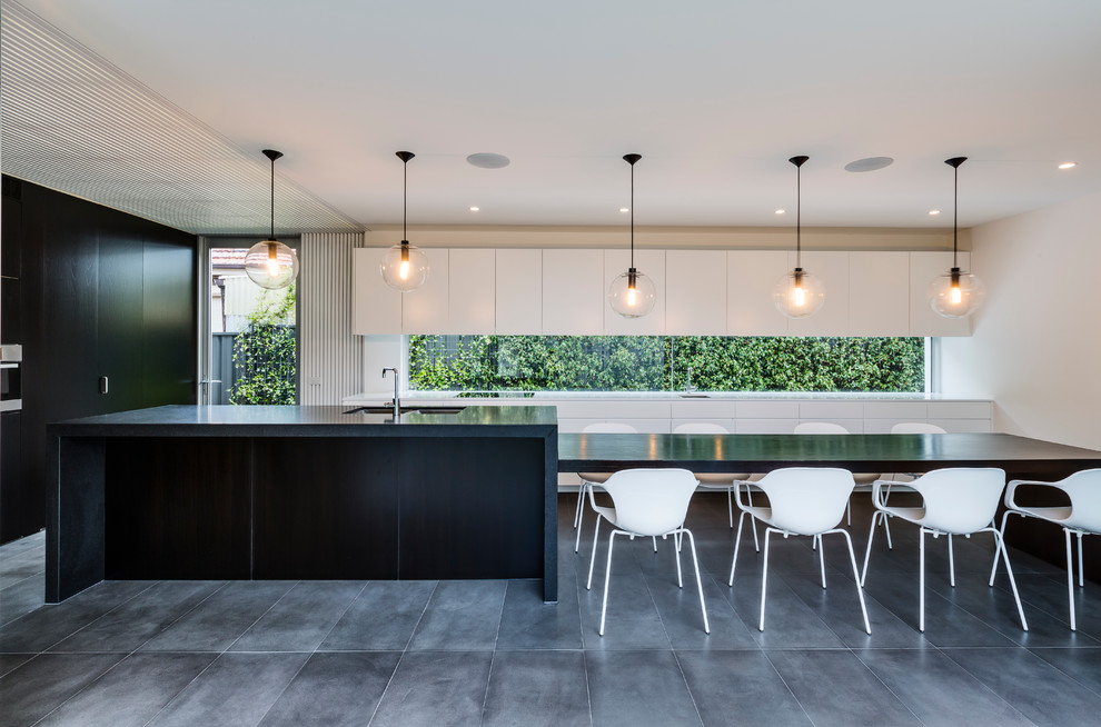 Photo of a contemporary galley eat-in kitchen in Sydney with an undermount sink, flat-panel cabinets, white cabinets, wood benchtops, an island, glass sheet splashback, stainless steel appliances, ceramic floors and black floor.