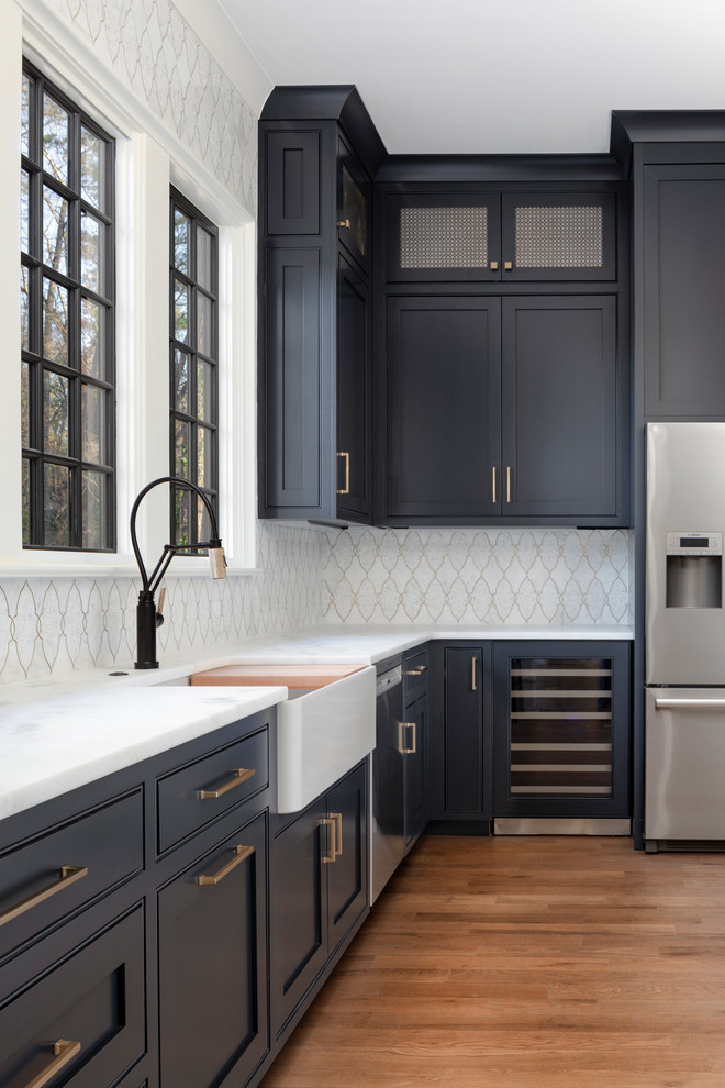Kitchen pantry - mid-sized traditional l-shaped medium tone wood floor and brown floor kitchen pantry idea in Charlotte with a farmhouse sink, blue cabinets, marble countertops, white backsplash, mosaic tile backsplash, stainless steel appliances and white countertops