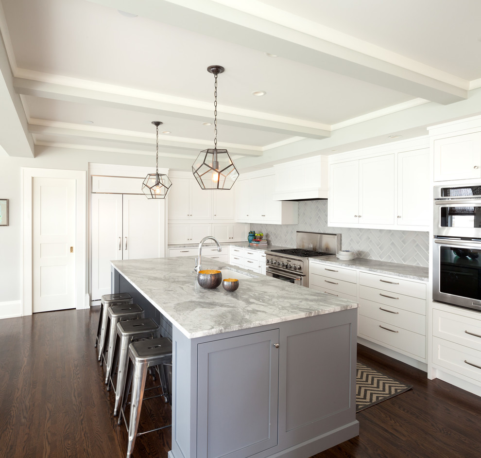 Inspiration for a transitional l-shaped dark wood floor eat-in kitchen remodel in Minneapolis with an undermount sink, shaker cabinets, white cabinets, marble countertops, gray backsplash, ceramic backsplash, stainless steel appliances and an island