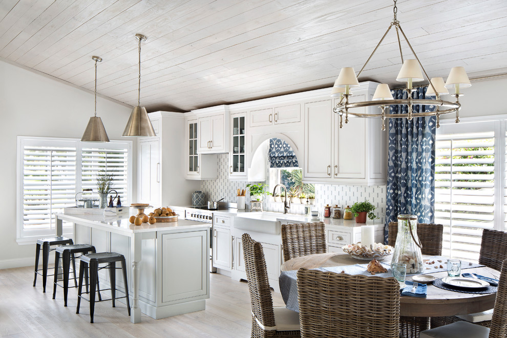 Mid-sized beach style single-wall porcelain tile open concept kitchen photo in Miami with a farmhouse sink, shaker cabinets, white cabinets, an island, quartz countertops, multicolored backsplash, glass tile backsplash and stainless steel appliances