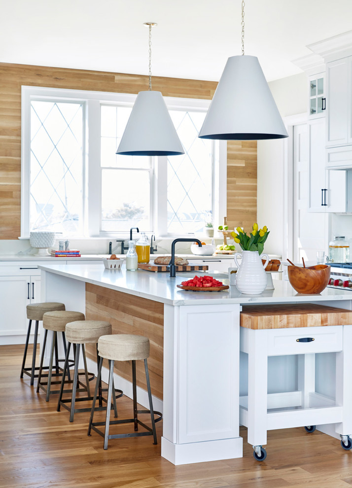 Example of a beach style light wood floor and beige floor kitchen design in New York with shaker cabinets, white cabinets, wood backsplash, stainless steel appliances, white countertops, beige backsplash, marble countertops and an island
