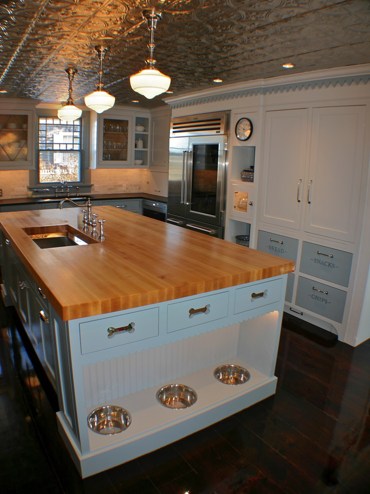 Elegant kitchen photo in Boston with an undermount sink, shaker cabinets, white cabinets, wood countertops, stainless steel appliances and brown countertops