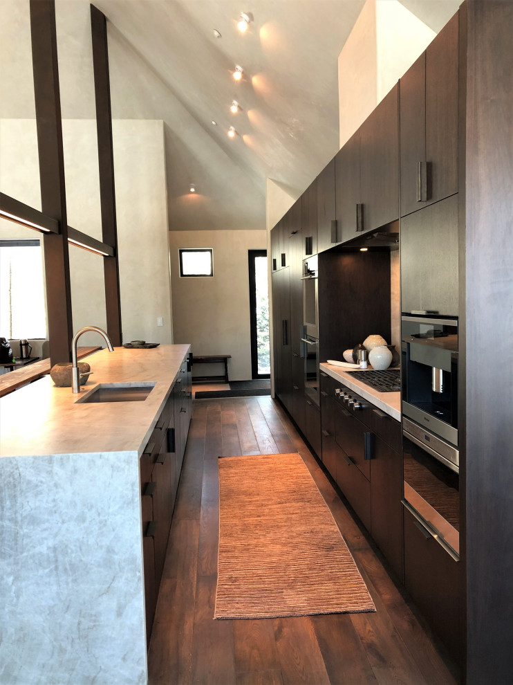 Open concept kitchen - large contemporary galley medium tone wood floor, brown floor and vaulted ceiling open concept kitchen idea in Other with an undermount sink, flat-panel cabinets, dark wood cabinets, colored appliances, an island and multicolored countertops