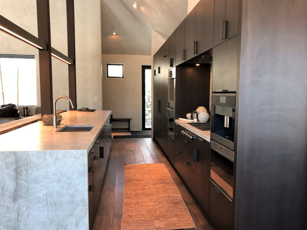 Inspiration for a large contemporary galley medium tone wood floor, brown floor and vaulted ceiling open concept kitchen remodel in Other with an undermount sink, flat-panel cabinets, dark wood cabinets, colored appliances, an island and multicolored countertops