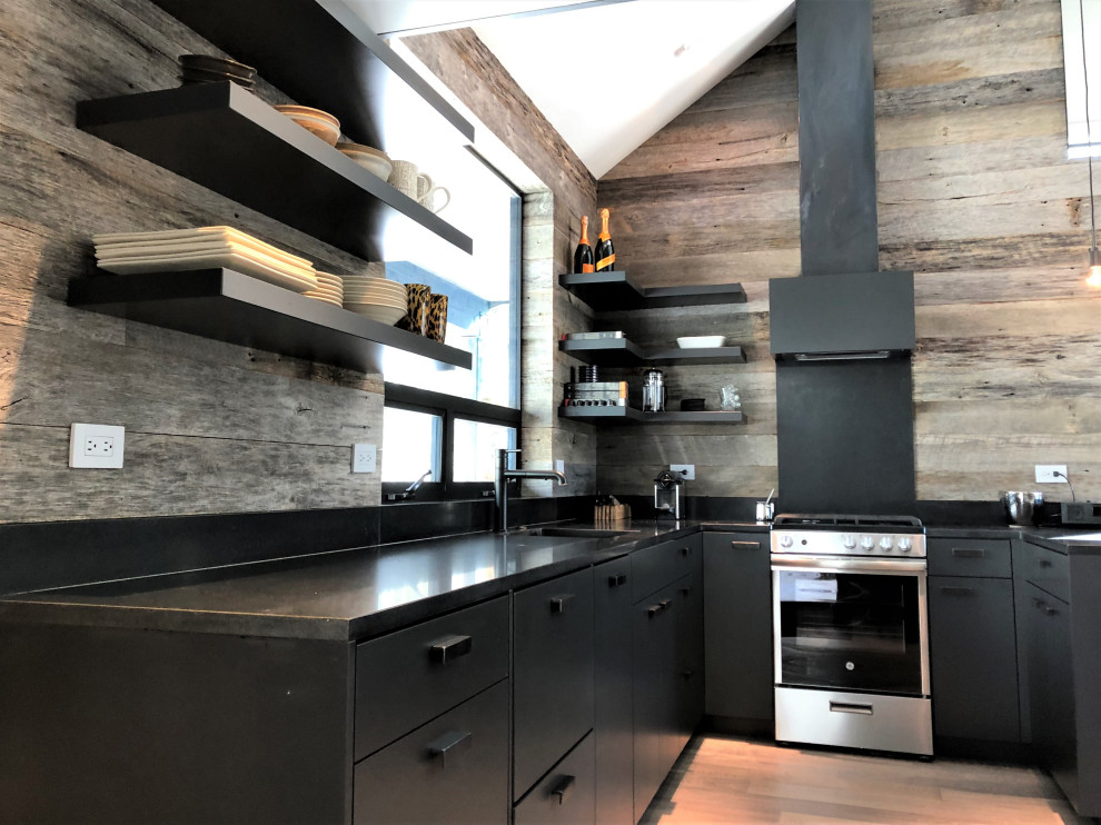 Inspiration for a mid-sized contemporary u-shaped light wood floor, orange floor and vaulted ceiling open concept kitchen remodel in Other with an undermount sink, flat-panel cabinets, black cabinets, brown backsplash, stainless steel appliances, a peninsula and brown countertops
