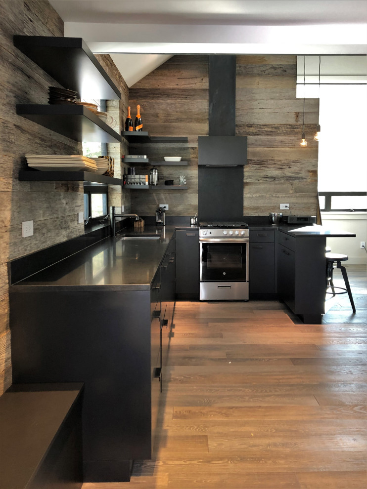 Open concept kitchen - mid-sized contemporary u-shaped light wood floor, orange floor and vaulted ceiling open concept kitchen idea in Other with an undermount sink, flat-panel cabinets, black cabinets, brown backsplash, stainless steel appliances, a peninsula and brown countertops