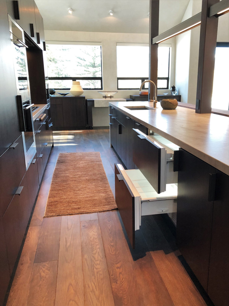 Large trendy galley medium tone wood floor, brown floor and vaulted ceiling open concept kitchen photo in Other with an undermount sink, flat-panel cabinets, dark wood cabinets, colored appliances, an island and multicolored countertops
