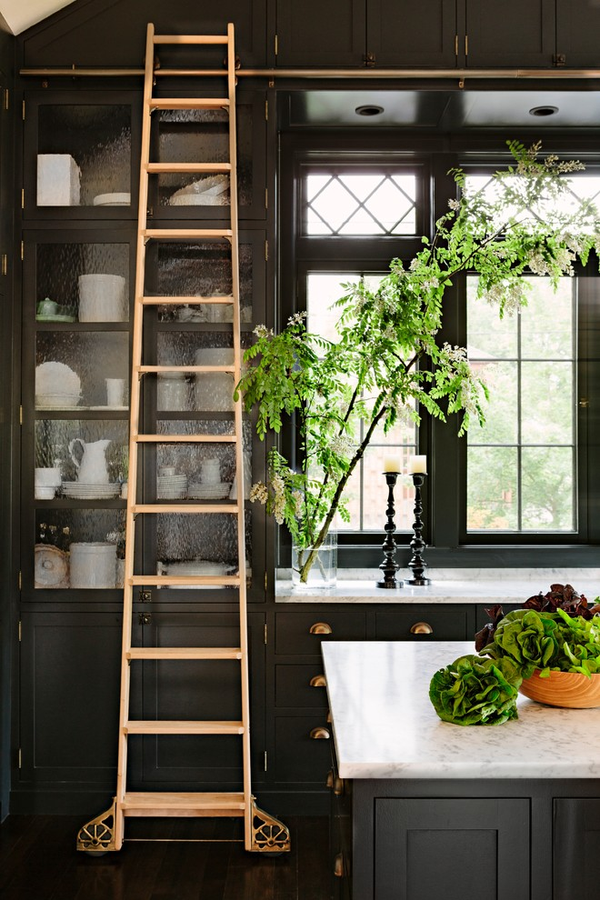 Kitchen - victorian dark wood floor kitchen idea in Portland with glass-front cabinets, black cabinets, marble countertops and an island