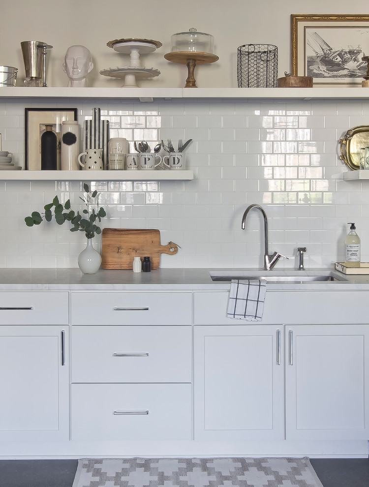 Inspiration for a small scandinavian l-shaped concrete floor eat-in kitchen remodel in Atlanta with an undermount sink, flat-panel cabinets, white cabinets, marble countertops, white backsplash, ceramic backsplash, stainless steel appliances and no island