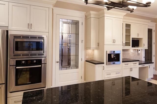 Aménagement d'une cuisine américaine classique en U avec un évier encastré, des portes de placard blanches, un plan de travail en granite, une crédence beige, une crédence en carrelage de pierre, un électroménager en acier inoxydable et un placard avec porte à panneau encastré.