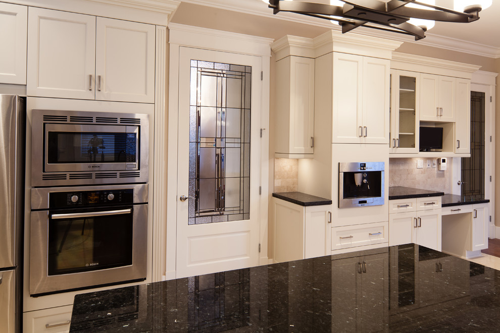 Eat-in kitchen - transitional u-shaped eat-in kitchen idea in Vancouver with an undermount sink, white cabinets, granite countertops, beige backsplash, stone tile backsplash, stainless steel appliances and recessed-panel cabinets