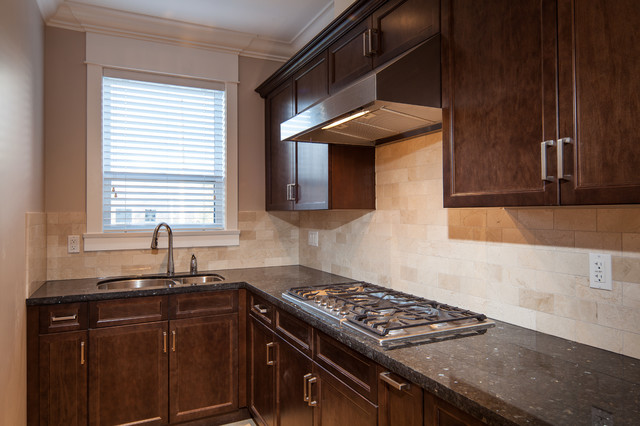 Imagen de cocina comedor en L, clásica renovada, con fregadero bajoencimera, armarios con paneles empotrados, puertas de armario de madera en tonos medios, encimera de granito, salpicadero beige, salpicadero de azulejos de piedra y electrodomésticos de acero inoxidable