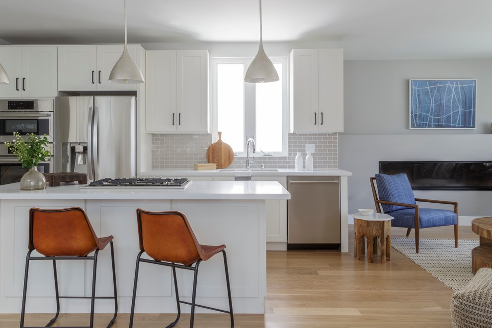 Open concept kitchen - small transitional galley open concept kitchen idea in San Francisco with an undermount sink, shaker cabinets, white cabinets, quartz countertops, gray backsplash, subway tile backsplash, stainless steel appliances and an island