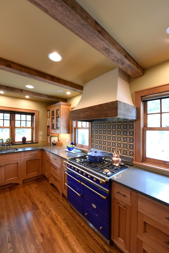 Inspiration for a mediterranean medium tone wood floor kitchen remodel in Other with recessed-panel cabinets, medium tone wood cabinets, multicolored backsplash and colored appliances