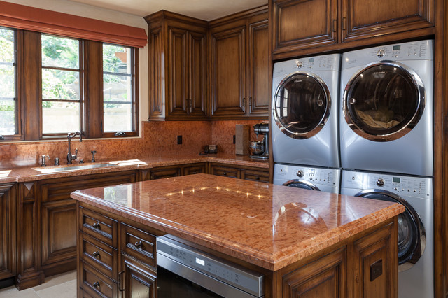 Example of a tuscan l-shaped kitchen design in Orange County with an undermount sink, raised-panel cabinets, dark wood cabinets and orange countertops