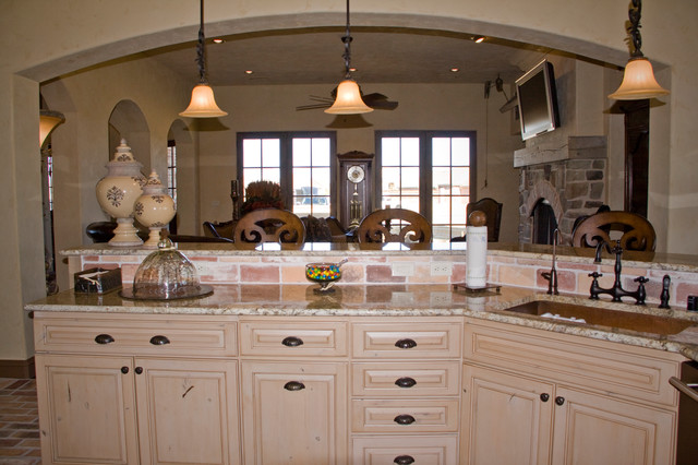 Eat-in kitchen - mediterranean brick floor eat-in kitchen idea in Austin with raised-panel cabinets, light wood cabinets, granite countertops, beige backsplash, stone tile backsplash and an island