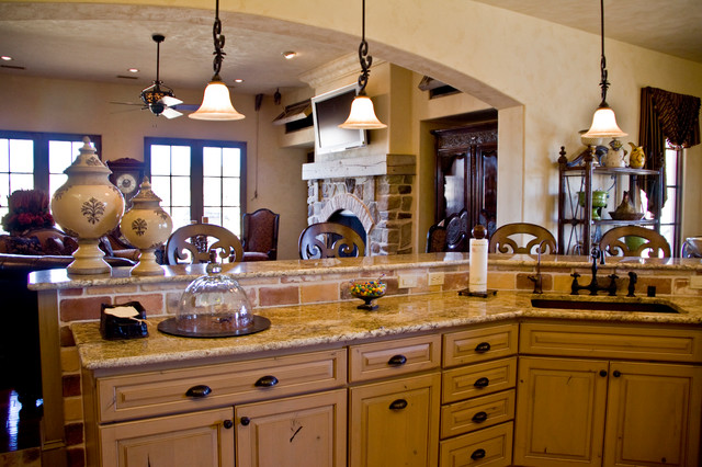 Example of a tuscan eat-in kitchen design in Austin with raised-panel cabinets, light wood cabinets, granite countertops, beige backsplash, stone tile backsplash and an island