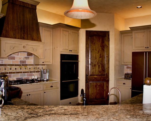 Inspiration for a rustic brick floor eat-in kitchen remodel in Austin with raised-panel cabinets, light wood cabinets, granite countertops, beige backsplash, stone tile backsplash and an island