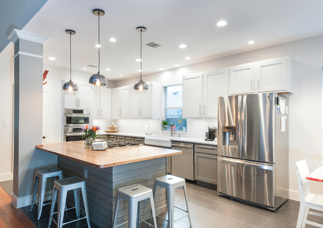 Example of a large trendy l-shaped ceramic floor open concept kitchen design in Austin with a farmhouse sink, shaker cabinets, white cabinets, wood countertops, white backsplash, ceramic backsplash, stainless steel appliances and an island
