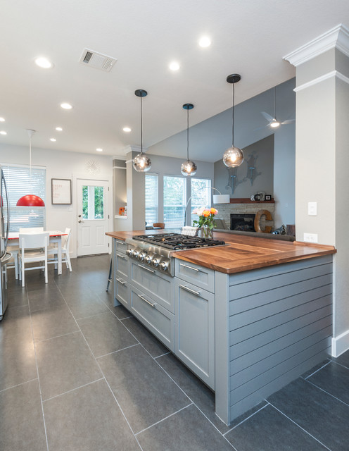 Open concept kitchen - large transitional l-shaped ceramic floor open concept kitchen idea in Austin with a farmhouse sink, shaker cabinets, white cabinets, wood countertops, white backsplash, ceramic backsplash, stainless steel appliances and an island