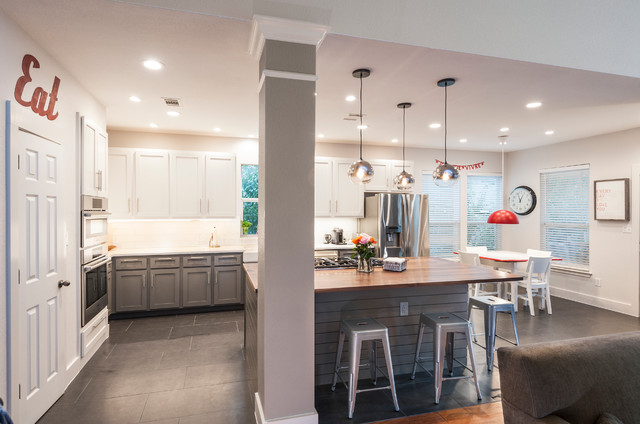 Example of a large transitional l-shaped ceramic floor open concept kitchen design in Austin with a farmhouse sink, shaker cabinets, white cabinets, quartz countertops, white backsplash, ceramic backsplash, stainless steel appliances and an island
