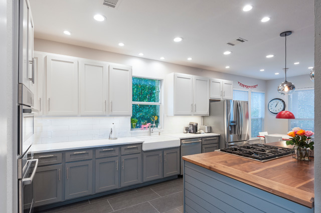 Large transitional l-shaped ceramic floor open concept kitchen photo in Austin with a farmhouse sink, shaker cabinets, white cabinets, wood countertops, white backsplash, ceramic backsplash, stainless steel appliances and an island