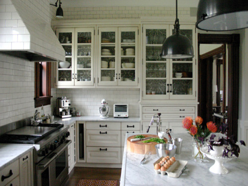 Large elegant u-shaped medium tone wood floor and brown floor kitchen photo in Chicago with a farmhouse sink, raised-panel cabinets, white cabinets, marble countertops, white backsplash, subway tile backsplash, stainless steel appliances, an island and white countertops