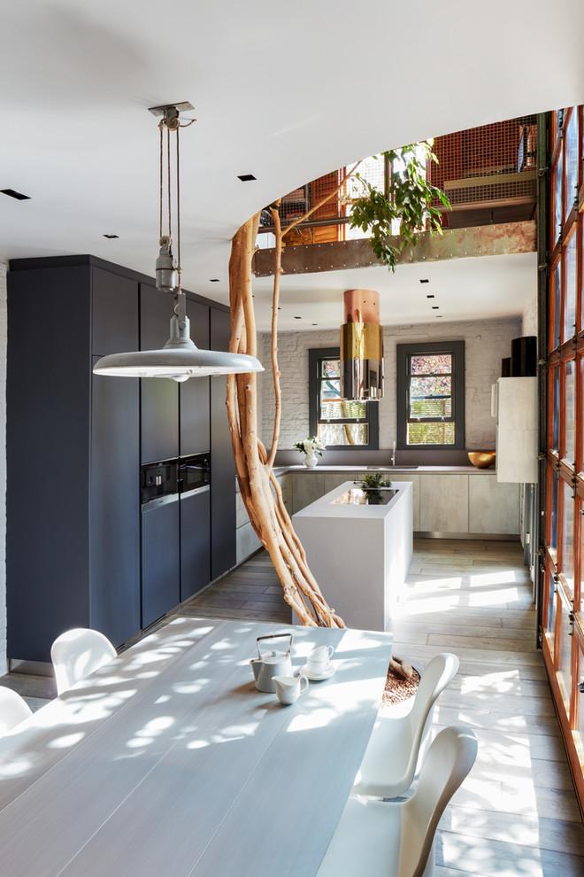 Trendy u-shaped light wood floor open concept kitchen photo in London with flat-panel cabinets, blue cabinets, white backsplash, brick backsplash, black appliances and an island