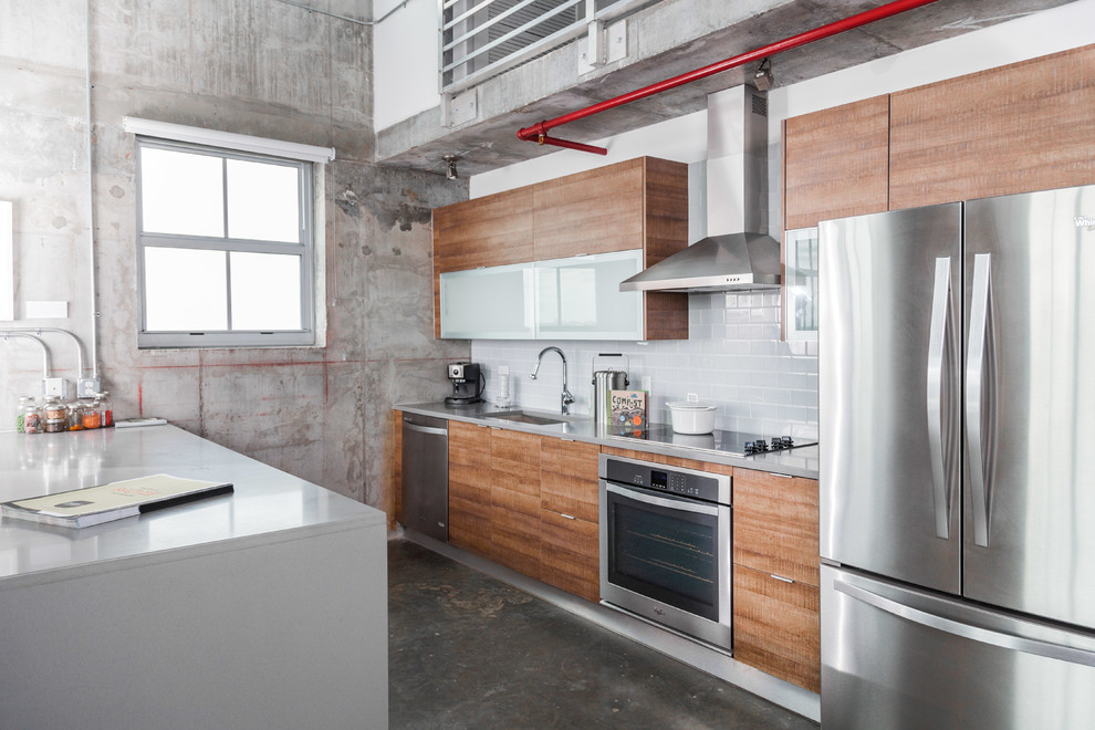 Example of an urban galley concrete floor kitchen design in Miami with an undermount sink, flat-panel cabinets, medium tone wood cabinets, gray backsplash, subway tile backsplash, stainless steel appliances and a peninsula