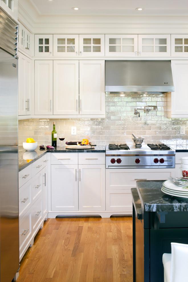 Klassische Küche mit Schrankfronten mit vertiefter Füllung, Küchengeräten aus Edelstahl, weißen Schränken, Küchenrückwand in Metallic und Rückwand aus Metrofliesen in Boston