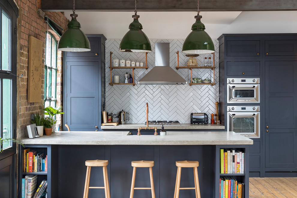 Example of a large urban galley medium tone wood floor and brown floor kitchen design in London with shaker cabinets, blue cabinets, gray backsplash, stainless steel appliances and a peninsula