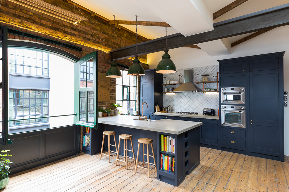 Example of a large urban galley medium tone wood floor and brown floor open concept kitchen design in London with a farmhouse sink, shaker cabinets, blue cabinets, concrete countertops, white backsplash, subway tile backsplash, stainless steel appliances and a peninsula