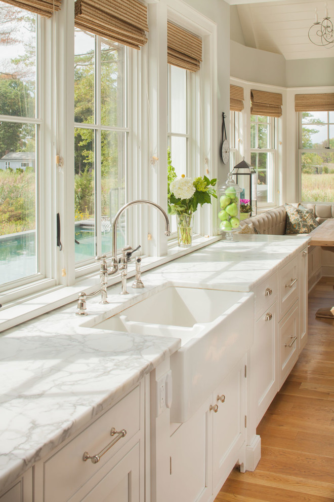 Example of a large coastal light wood floor eat-in kitchen design in New York with a farmhouse sink, recessed-panel cabinets, white cabinets, marble countertops and white countertops
