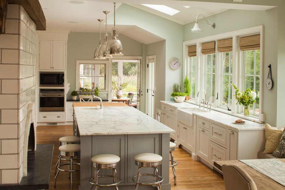 Example of a large beach style l-shaped light wood floor eat-in kitchen design in New York with a farmhouse sink, recessed-panel cabinets, white cabinets, marble countertops, white backsplash, stainless steel appliances and an island