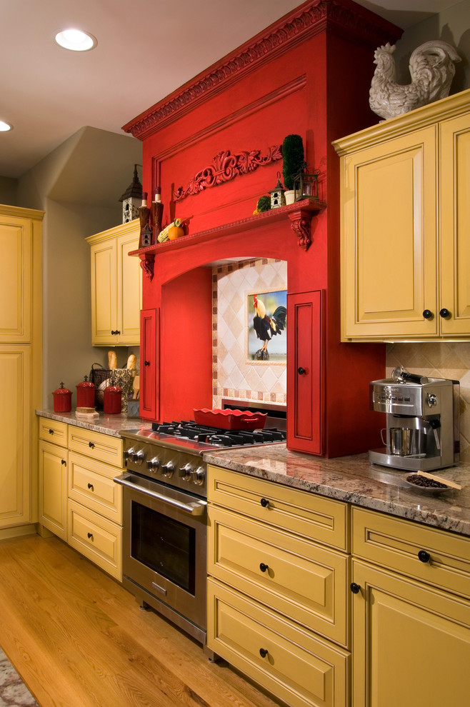 Example of a cottage kitchen design in New York with raised-panel cabinets, yellow cabinets and granite countertops