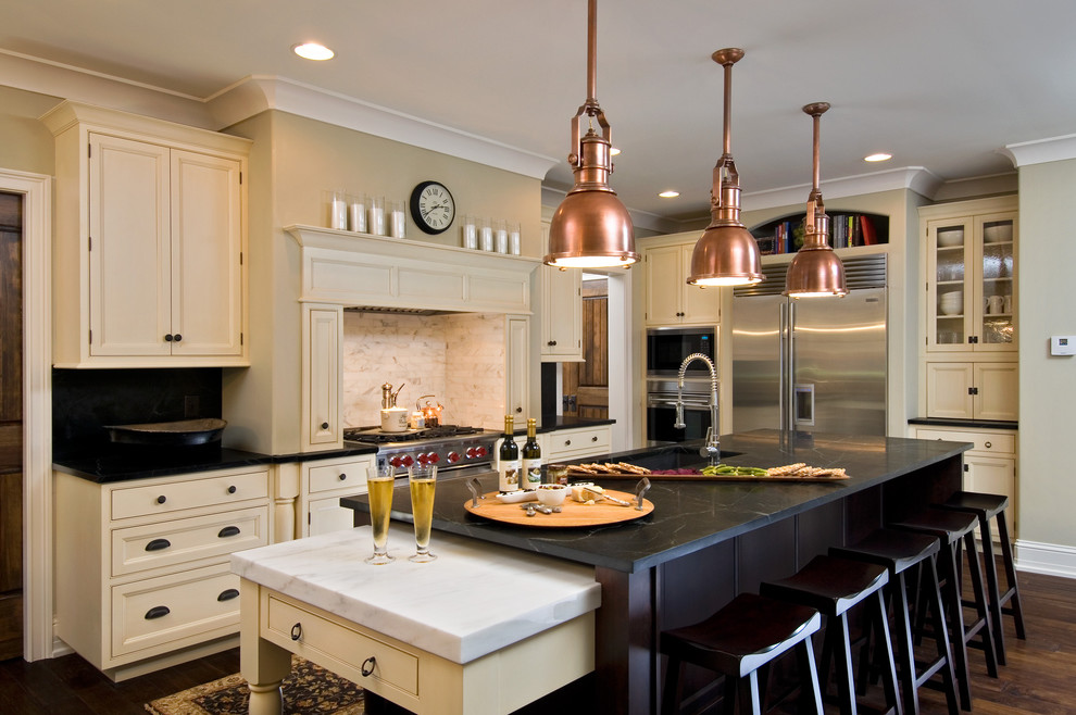 Kitchen - traditional kitchen idea in New York with beaded inset cabinets, stainless steel appliances, soapstone countertops, beige cabinets, white backsplash and stone tile backsplash