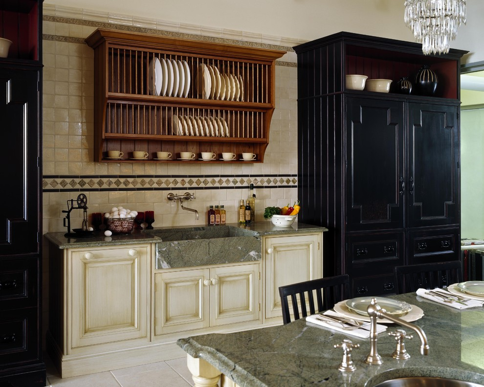 Elegant kitchen photo in Boston with an integrated sink, black cabinets and granite countertops